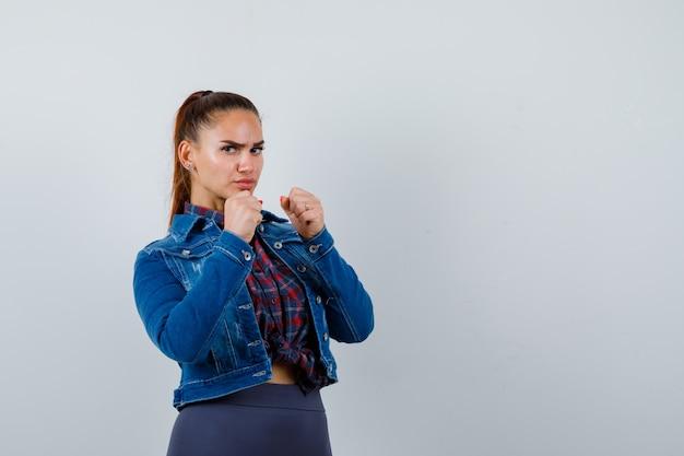 Jonge vrouw die zijwaarts in gevecht staat, poseert in geruit hemd, spijkerjasje en ziet er serieus uit.