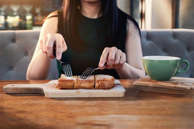 Jonge vrouw die zoet dessert in café of restaurant eten. vooraanzicht. bijgesneden afbeelding