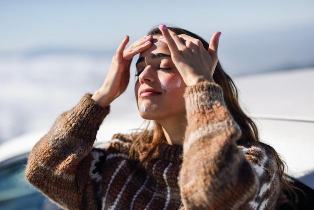 Jonge vrouw die zonnescherm op haar gezicht in sneeuwlandschap toepast