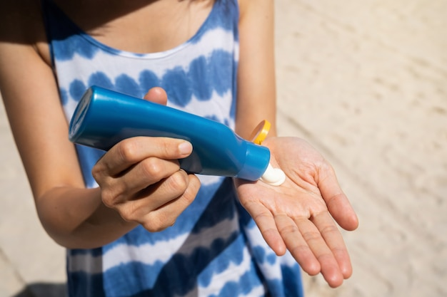 Jonge vrouw die zonnescherm op haar toepassen bij het tropische strand