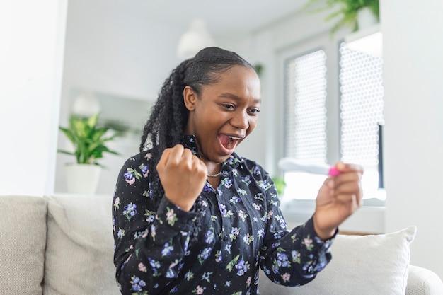 Jonge vrouw die zwangerschapstest in geluk bekijkt. eindelijk zwanger. aantrekkelijke zwarte vrouwen kijken naar zwangerschapstest en glimlachen terwijl ze thuis op de bank zitten