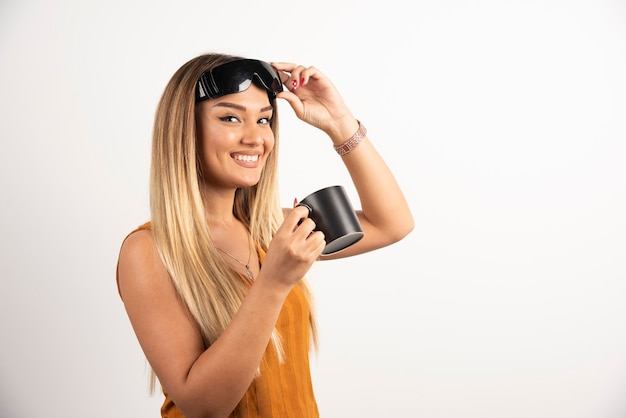 Jonge vrouw die zwarte kop houdt en beschermende brillen draagt.
