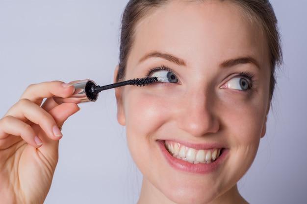 Jonge vrouw die zwarte mascara toepast.