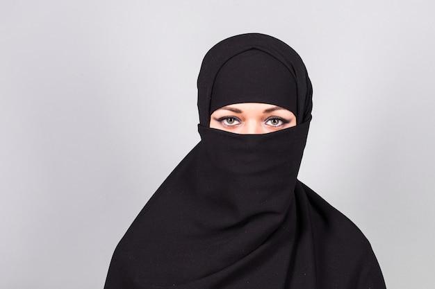 Jonge vrouw die zwarte niqab op achtergrond draagt.