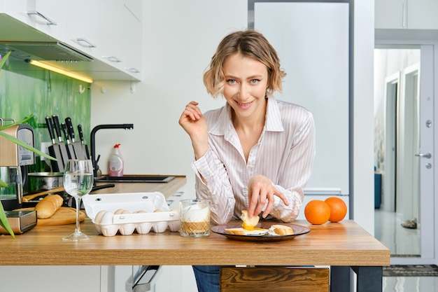 Jonge vrouw dipt toast in gebakken ei