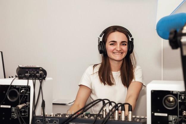 Jonge vrouw dj-radiopresentator in studio met koptelefoon, microfoon, klinkt gemengde console en praat nieuws live