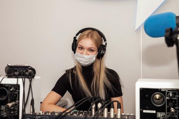 Jonge vrouw dj-radiopresentator in studio met medisch masker, koptelefoon, microfoon, klinkt gemengde console en praat nieuws live