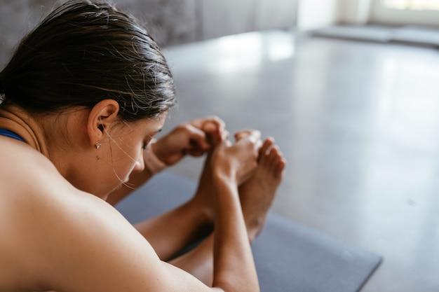 Jonge vrouw doen yoga pose oefening thuis, gezonde levensstijl