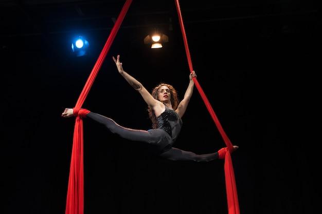 Jonge vrouw doet acrobatiek op een zwarte achtergrond