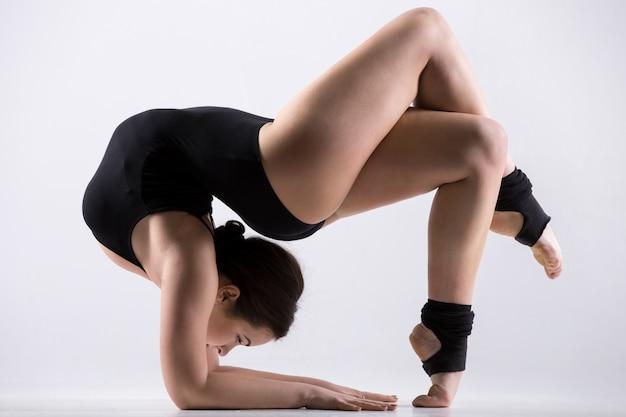 Jonge vrouw doet acrobatische oefening