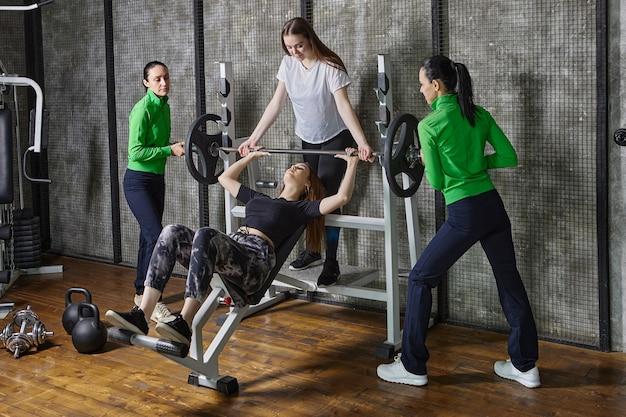 Jonge vrouw doet bankdrukken in de sportschool met steun van teamgenoten