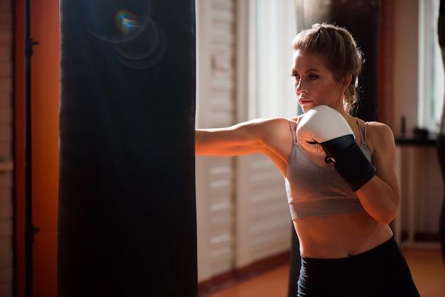Jonge vrouw doet bokstraining in de sportschool, ze draagt bokshandschoenen en slaat een bokszak.
