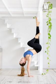 Jonge vrouw doet een handstand stretch yoga pose met behulp van een houten frame voor ondersteuning terwijl ze balanceert op haar handen