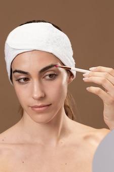 Jonge vrouw doet een schoonheidsbehandeling voor zichzelf