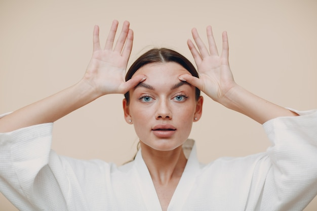 Jonge vrouw doet gezicht gebouw gezicht gymnastiek zelfmassage en verjongende oefening