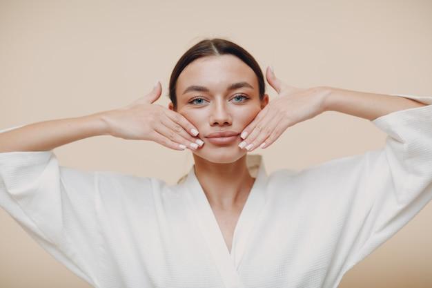 Jonge vrouw doet gezicht gebouw gezicht gymnastiek zelfmassage en verjongende oefeningen aanraken van de lippen