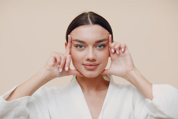 Jonge vrouw doet gezicht gebouw gezicht gymnastiek zelfmassage en verjongende oefeningen