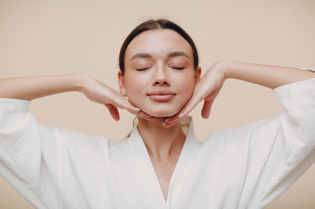 Jonge vrouw doet gezicht gebouw yoga gezicht gymnastiek zelfmassage en verjongende oefeningen