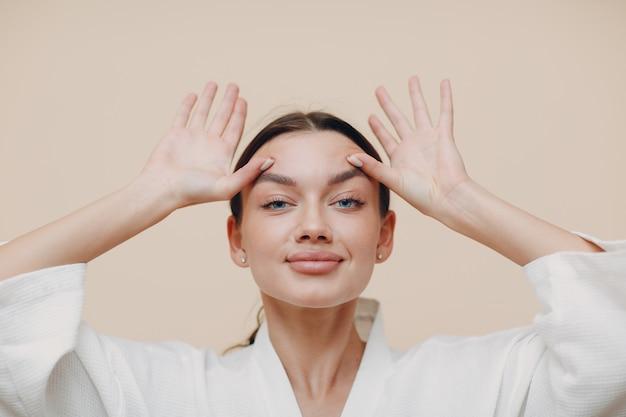 Jonge vrouw doet gezichtsgymnastiek zelfmassage en verjongende oefeningen
