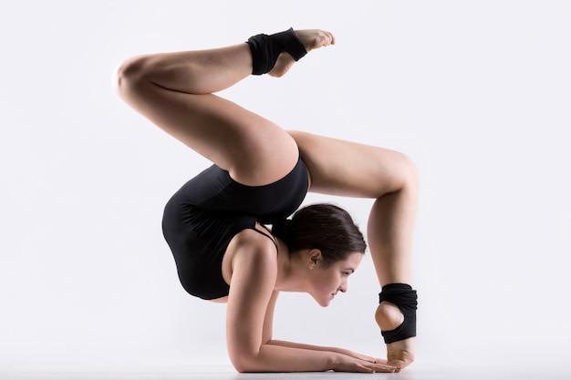 Jonge vrouw doet gymnastiek handstand oefening