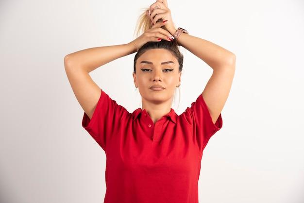 Jonge vrouw doet haar haar op een witte achtergrond.