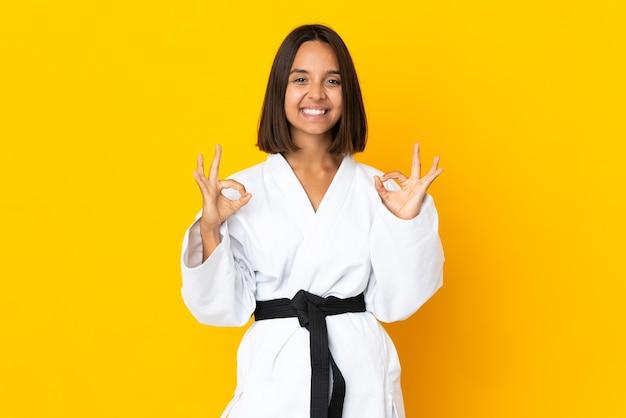 Jonge vrouw doet karate geïsoleerd op een gele achtergrond met een ok teken met vingers