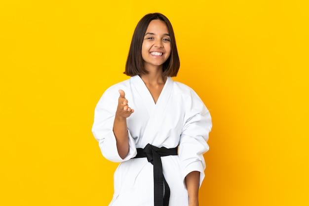 Jonge vrouw doet karate geïsoleerd op gele achtergrond handen schudden voor het sluiten van een goede deal