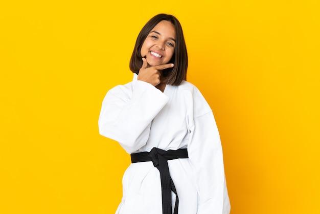 Jonge vrouw doet karate geïsoleerd op gele achtergrond lachend