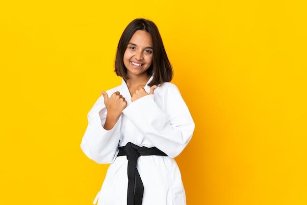 Jonge vrouw doet karate geïsoleerd op gele achtergrond met duim omhoog gebaar en lachend