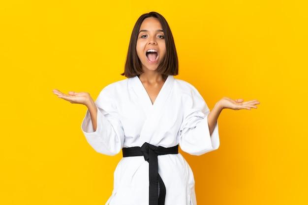 Jonge vrouw doet karate geïsoleerd op gele achtergrond met geschokte gezichtsuitdrukking