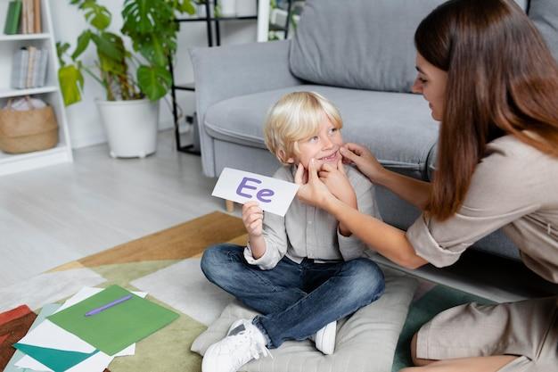 Jonge vrouw doet logopedie met een kleine blonde jongen