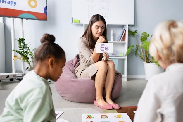 Jonge vrouw doet logopedie met kinderen