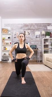 Jonge vrouw doet lunges thuis voor een gezond lichaam. fitness training.