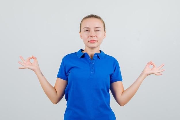 Jonge vrouw doet meditatie en knipogen oog in blauw t-shirt