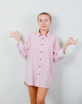 Jonge vrouw doet meditatie en knipogen oog in roze shirt
