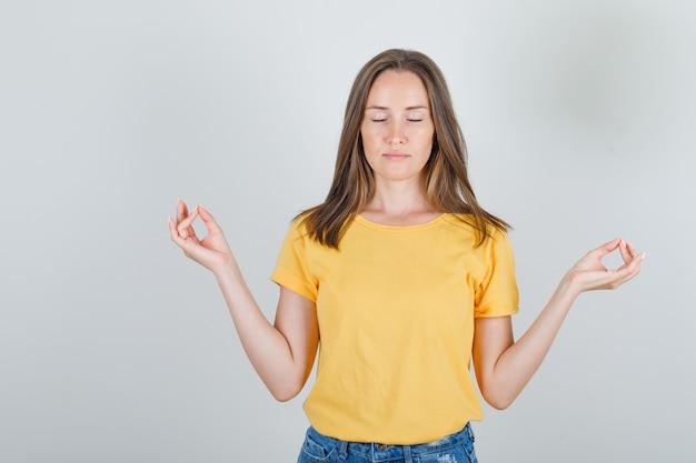 Jonge vrouw doet meditatie met gesloten ogen in t-shirt, korte broek en op zoek ontspannen