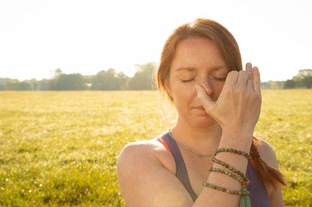 Jonge vrouw doet meditatie-oefeningen buitenshuis met kopieerruimte