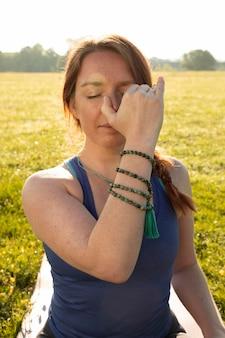 Jonge vrouw doet meditatie-oefeningen buitenshuis