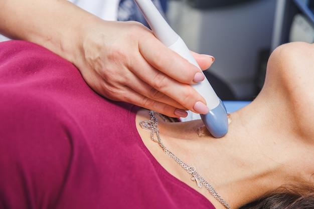 Jonge vrouw doet nek echografie onderzoek in het ziekenhuis