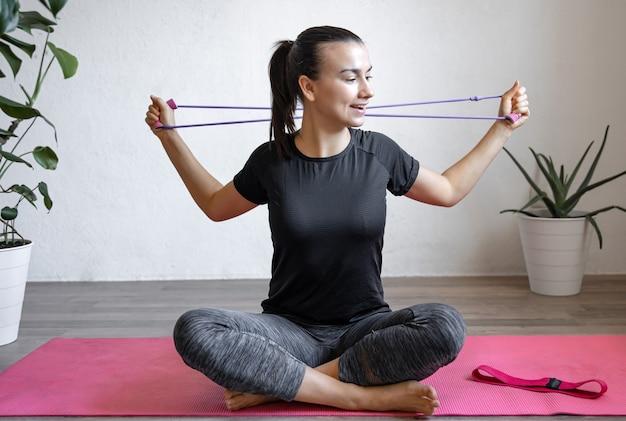 Jonge vrouw doet oefeningen met een fitness elastische band thuis