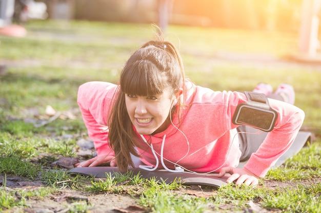 Jonge vrouw doet push-ups oefeningen in het park.