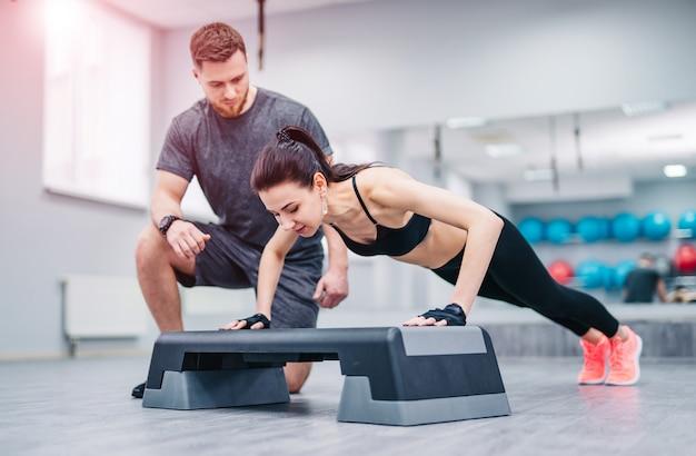 Jonge vrouw doet push-ups vanuit stand en een trainer controleert het in sportclub.