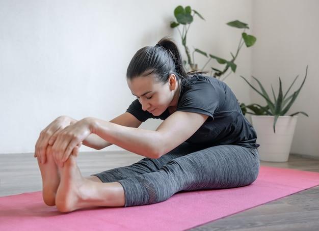 Jonge vrouw doet rekoefeningen thuis op het tapijt.