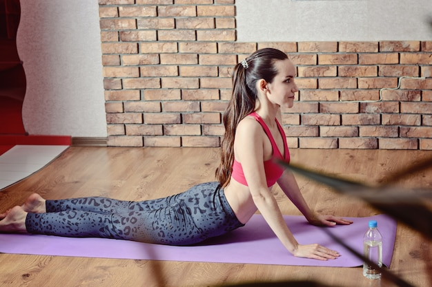 Jonge vrouw doet rekoefeningen van de benen en terug op een paarse fitness mat. het concept van thuisfitness