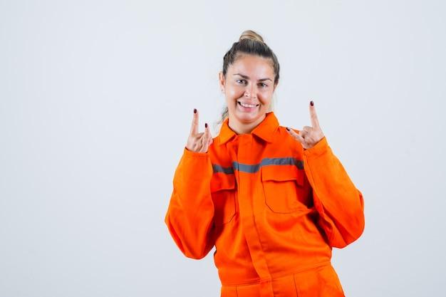 Jonge vrouw doet rock in roll-gebaar in uniform van de werknemer en kijkt vrolijk, vooraanzicht.