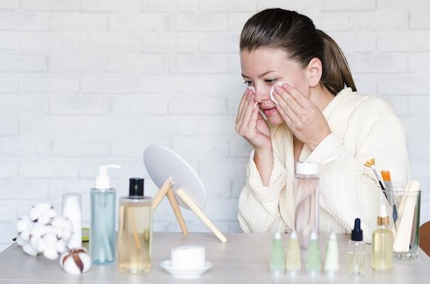 Jonge vrouw doet spa, wellness-behandelingen, procedures thuis met behulp van natuurlijke cosmetica.