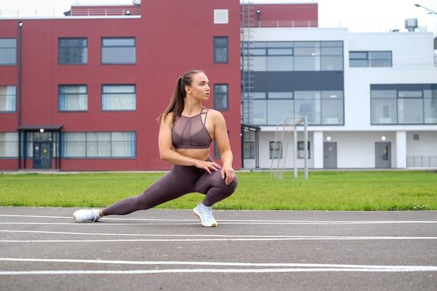Jonge vrouw doet sporttraining in het stadion buiten met sportuitrusting. levensstijl en training oefening voor bodybuilding en gezond.