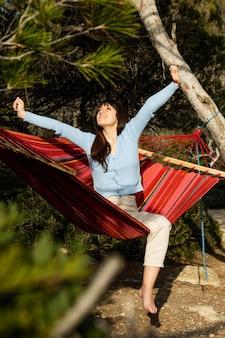 Jonge vrouw doet stretching zittend in een hangmat, glimlachend naar de lucht