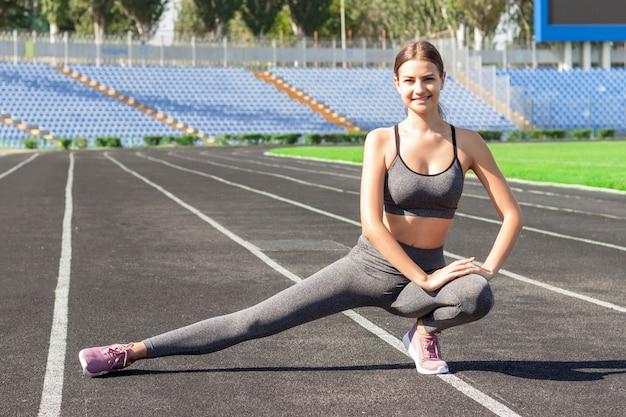 Jonge vrouw doet warming-up en streching voordat actieve training