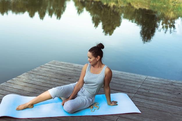 Jonge vrouw doet yoga aan het meer